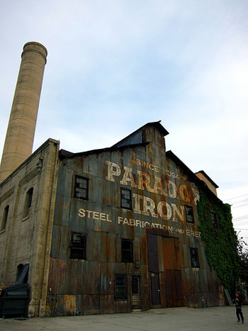 "A photograph of the outside of a factory building and smokestack. The building has a sign painted on it that reads: ""Paradox Iron: Steel Fabrication."""