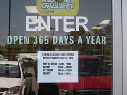 """A photograph of a store window that reads: """"ENTER: Open 365 days a year."""" Taped on to the window are the stores closing times and dates."""