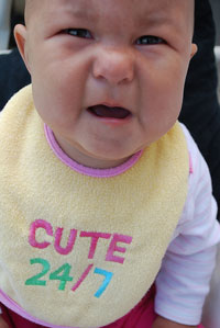 """A photograph of an angry looking baby wearing a bib that says """"Cute 24/7."""""""