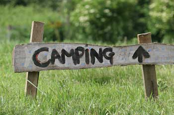 "A photograph of a sign that reads: ""camping"" with an arrow pointing forward. It is a handwritten sign composed of wood scraps."