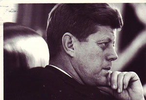 A photograph of President John F. Kennedy seated at his desk in the oval office