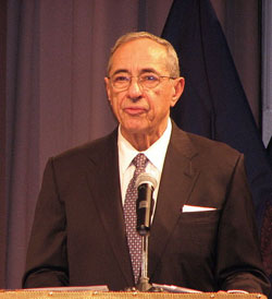 A photograph of New York Governor Mario Cuomo standing a t a podium and speaking into a microphone