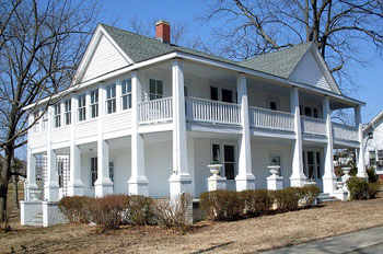 A photograph of a two story house with a wraparound porch