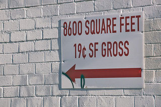 "A sign on an outdoor wall that reads ""8600 Square Feet 19¢ SF Gross"""