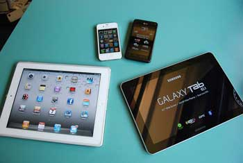 A photograph of several devices on a table. They are smart phones and tablets.