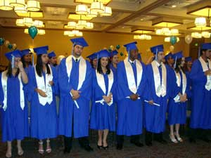 A photograph of students at a graduation. They are all wearing typical graduation apparel.