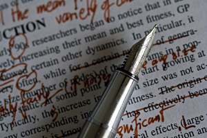 A close-up picture of an elegant fountain pen. The page underneath the pen is an essay on physical fitness, covered with revisions in a dark red ink.