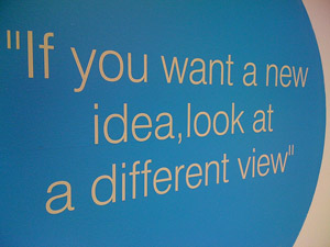 "A mural with a text bubble that says ""if you want a new idea, look at a different view."""