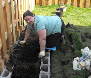 A woman working on building a plant bed in her. She's moved a row of cinder blocks into position. Her hands are covered with dirt, but she looks satisfied with her work.