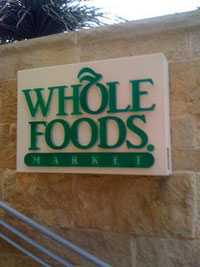 """A photograph of a """"Whole Foods Market"""" sign outside of the store in Austin, TX"""