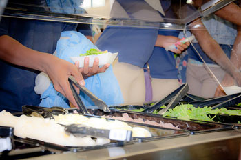 A photograph of students moving through a cafeteria line. They are reaching in for food items with tongs.