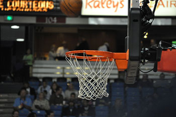 A photograph of an indoor basketball hoop and net taken up close