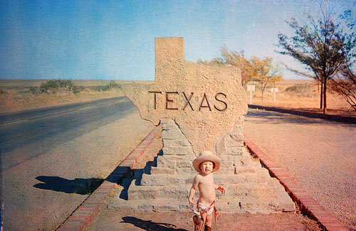 "A photograph of a sign in the shape of Texas with the word ""Texas ""carved into it. There is a baby standing in front of it wearing a diaper, a cowboy hat, boots, and wearing a toy pistol belt."