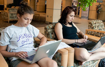 A photograph of two female students working on laptops in a school seating area