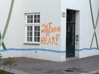 """photo of a spraypainted message on a wall that reads """"The revolution is hear"""""""