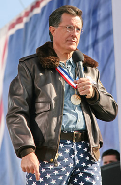 A picture of Stephen Colbert wearing a bomber jacket, star-covered pants, a la the U.S. flag, and a medal around his neck.