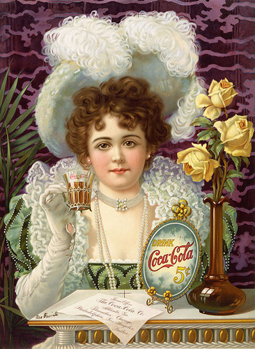 """An 1890s advertising poster shows a woman in fancy clothes (vaguely influenced by 16th- and 17th-century styles) drinking Coke. The card on the table says """"Home Office, The Coca-Cola Co. Atlanta, Ga. Branches: Chicago, Philadelphia, Los Angeles, Dallas"""". There are cross-shaped color registration marks near the bottom-center and top-center (which presumably would have been removed for a production print run). Someone has crudely written on it at lower left (with a fountain pen that was apparently leaking), """"Our Favorite"""" [sic]."""