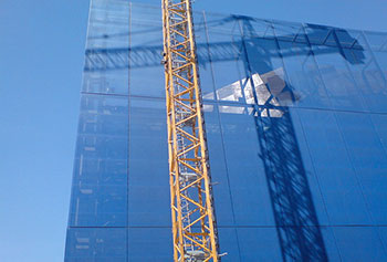 A photograph of a crane next to a building that is under construction.