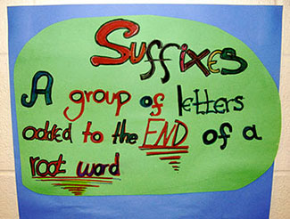 "A handmade sign that reads ""Suffixes: A group of letters added to the end of a root word."