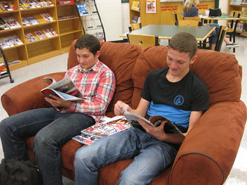 A photograph of two young men looking at magazines in a library.