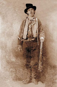 A portrait of the famous outlaw, Billy the Kid. He is a young man wearing a top hat. He is wearing a pistol belt and holding a rifle.