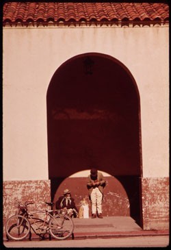 A photograph of the outside of a building in old San Antonio. There are two men talking under an awning and a bicycle propped up near them.