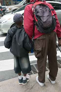 A photograph of a father and son waitng for a crossing light on a street corner. They are holding hands.