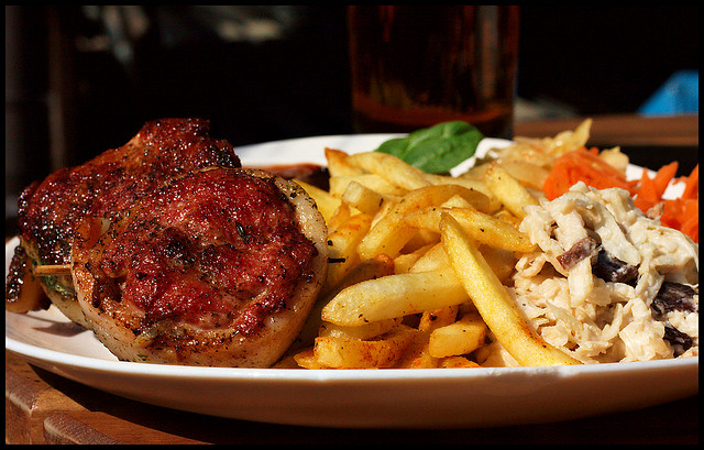 A photograph of a main course of a dinner. It is a steak, French Fries, and a salad