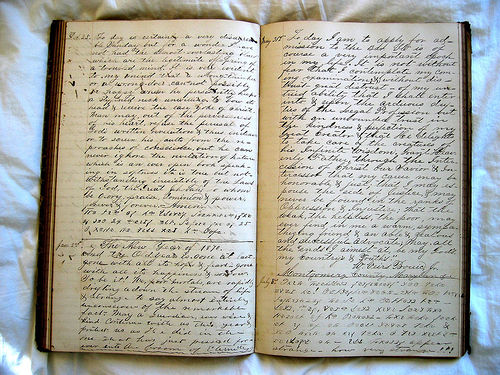 A photograph of an open diary with many lines of handwritten text on the pages.