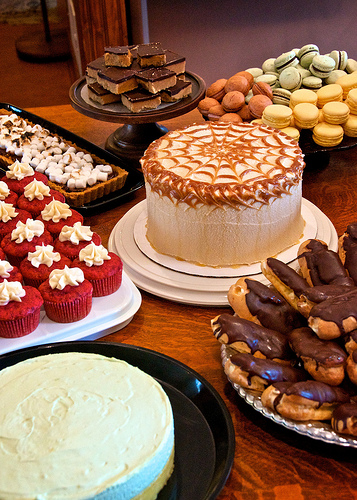 A photograph of a dessert table. There are cakes, cupcakes, éclairs, brownies, and cookies.