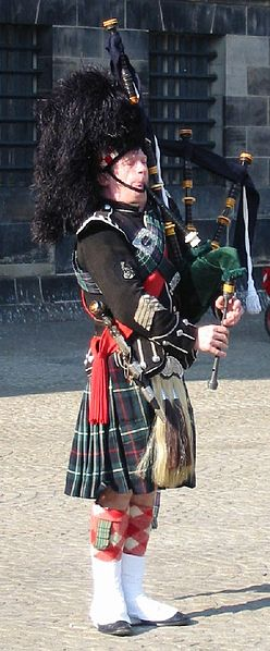 A photograph of a Scottish Bagpiper wearing full ceremonial garb, fur hat, and kilt