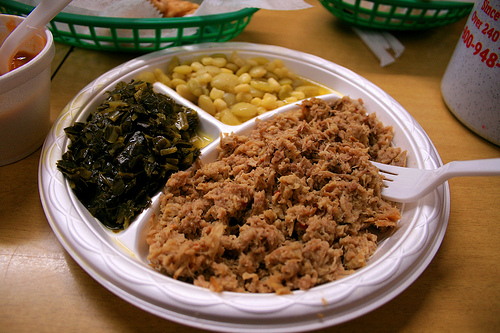 A photograph of a barbeque dinner of shredded pork, greens, and beans