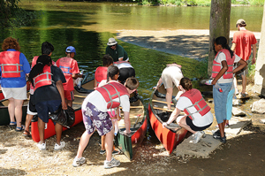 A photograph of a group of campers getting ready to go canoeing.