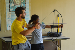 A photograph of a young adult using a bow and arrow while being assisted by an adult male.