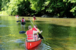 A photograph of campers canoeing on a river.