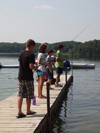A photograph of several young people fishing from a pier, on a lake.