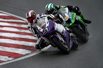 A photograph of two racing motorcycles going into a turn.