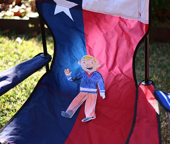 photo the paper cut-out character Flat Stanley sitting in a camping chair designed with the colors of the Texas flag