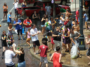A photograph of a crowd of people on a street corner involved in an giant water balloon fight.