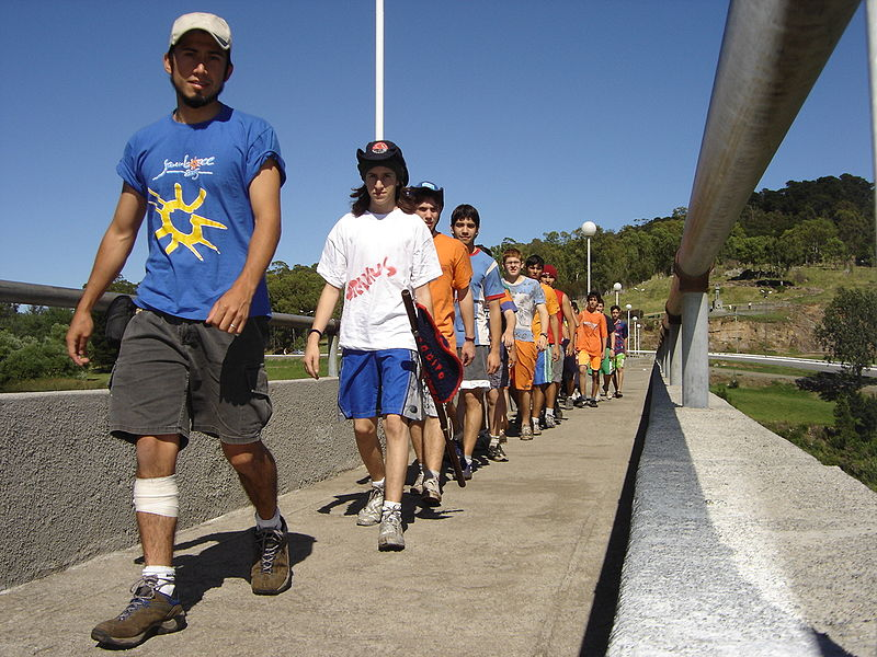 A photograph of a group of teenagers walking across a bridge in a single file line