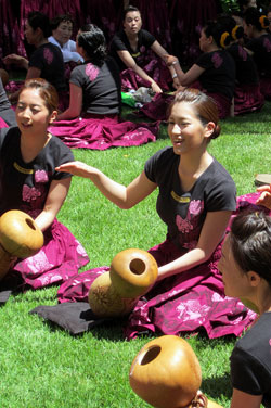 A photo of several young women all dressed in decorated t-shirts and pinkish/purple floral skirts as they sit in a grassy area and play drums shaped liked hourglasses