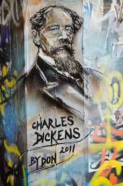 A mural of Charles dickens painted on graffitied wall of a building.