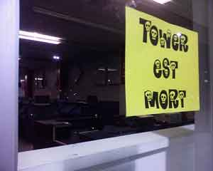 "A photo of the word ""tower est mort"" drawn on a yellow sheet of paper and taped to a window."