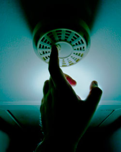 A close-up image of a hand testing a smoke detector. The lighting is strangely dark and mysterious for a common thing like a smoke detector.