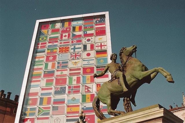 many flags from around the world appear on a towering rectangular wall. A sculpture of a horseman on a stallion appears at the forefront on the right side