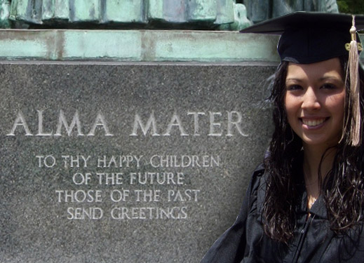 Young woman graduating from college. Behind her, a plaque reads: 'Alma Mater: To Thy Happy Children of the Future, Those of the Past Send Greetings.'