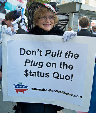 "At a political rally, an older woman dressed in fancy dress clothes carries a sign that says ""Don't pull the plug on the status quo! Billionaires for Wealth Care dot com."