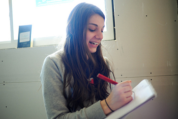 A teenaged girl smiling and writing in a notebook