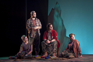 A scene from a modern interpretation of As You Like It—four characters look to the right against a stark blue background, the floor littered with discarded cans.