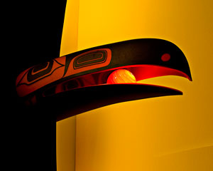 A vivid image in glowing reds and yellows. A huge raven's beak holds a luminescent yellow sphere.